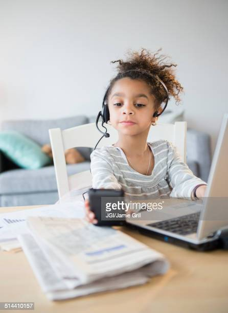 African American girl using headset, cell phone and laptop