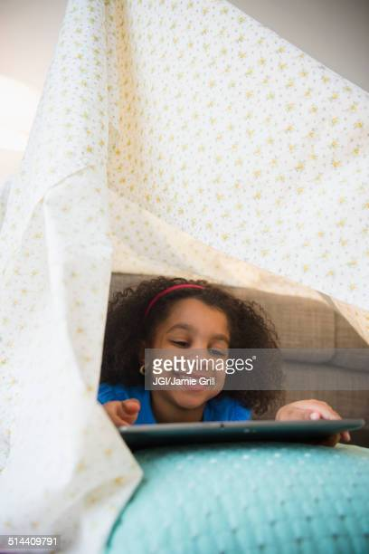 African American girl using tablet computer in blanket fort