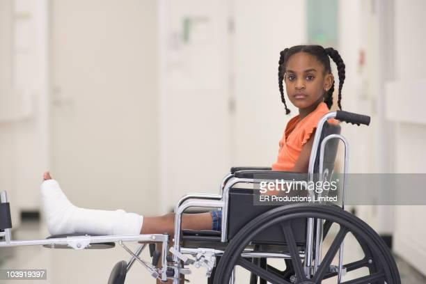 African American girl with broken leg sitting in wheelchair
