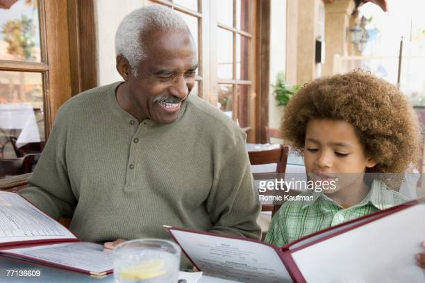 African American grandfather and grandson at restaurant