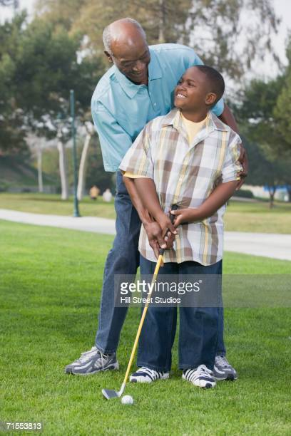 African American grandfather and grandson playing golf