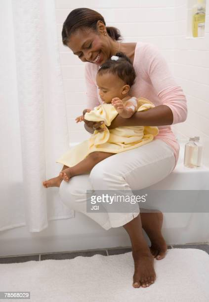 African American grandmother drying off baby
