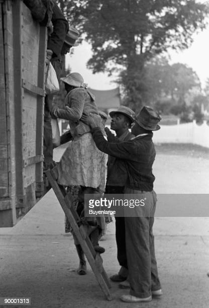 African American Helps a woman on board the migratory worker truck