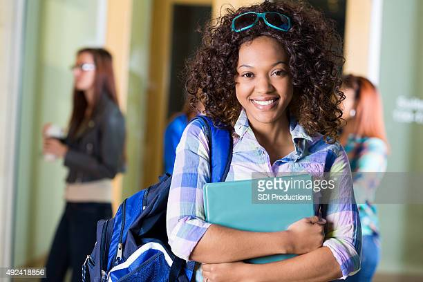 African American high school girl smiling while standing in hallway