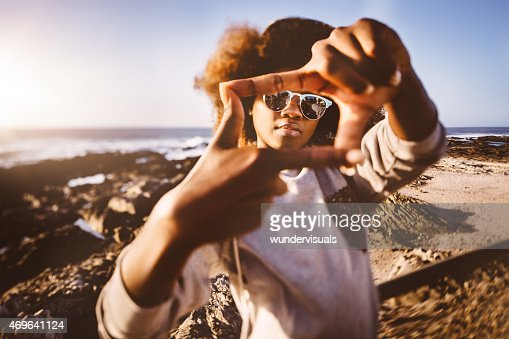 African American hipster teen at beach making frame with fingers