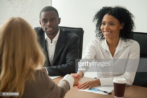 African american hr team welcoming female applicant at job interview : Stock Photo