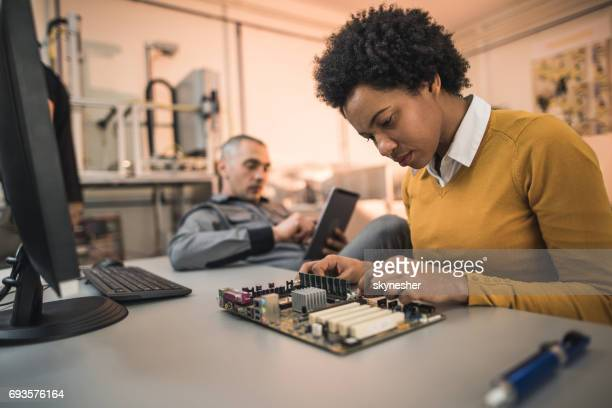 African American IT technician repairing components of a mother board.