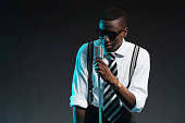 Retro african american jazz singer with microphone. Wearing shirt and tie and sunglasses. Studio shot.