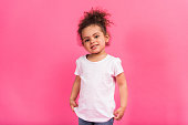 Smiling happy African american kid in white shirt standing isolated on pink