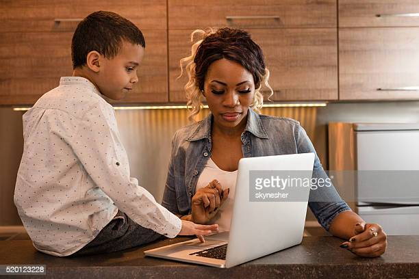 African American little boy and his mother using laptop.