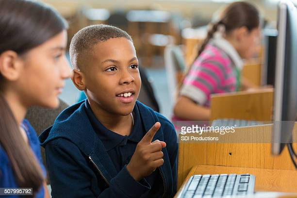 African American little boy pointing at computer screen in library
