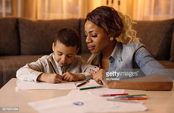 African American little boy sketching with his mother at home.