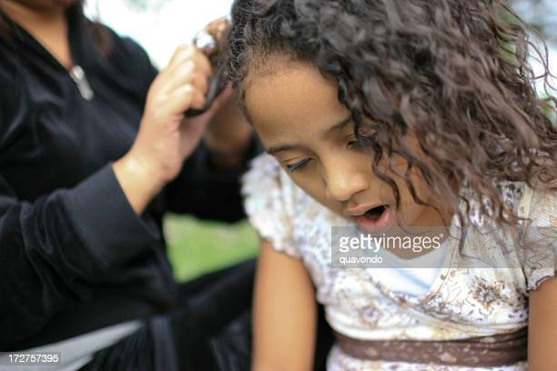 African American Little Girl in Pain, Mom Braiding Hair