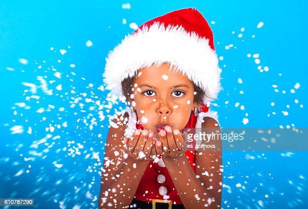 African American little girl in Santa Claus hat blowing snowflakes