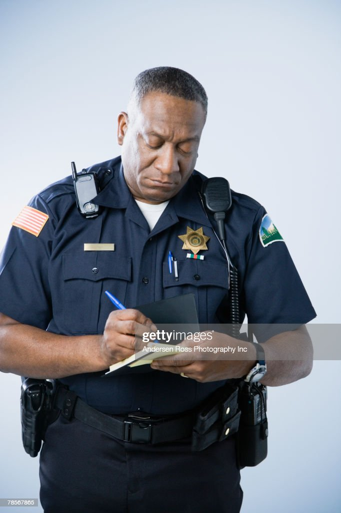 Police Officer Writing Traffic Ticket To Woman Sitting In Car