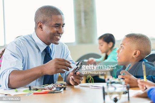 Afro-americano maschio insegnante utilizzando set di robotica in elementare classe