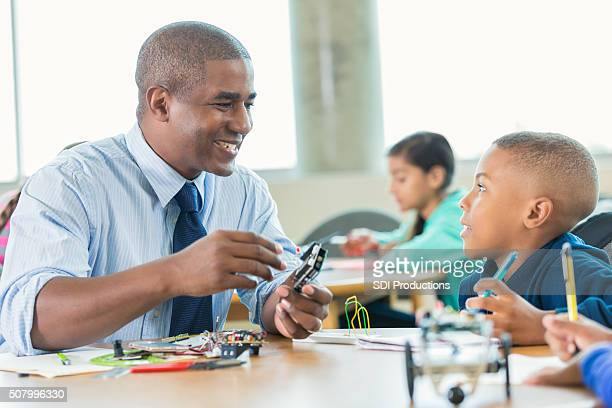 African American male teacher using robotics kit in elementary class