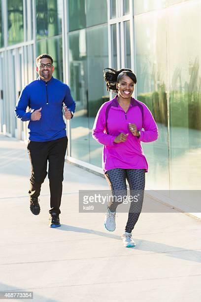 African American man and woman jogging on sidewalk