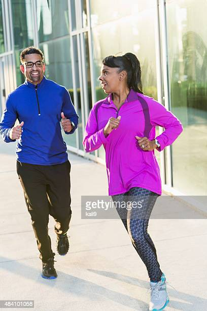 African American man and woman jogging on sidewalk