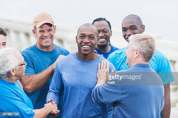 African American man being congratulated by friends