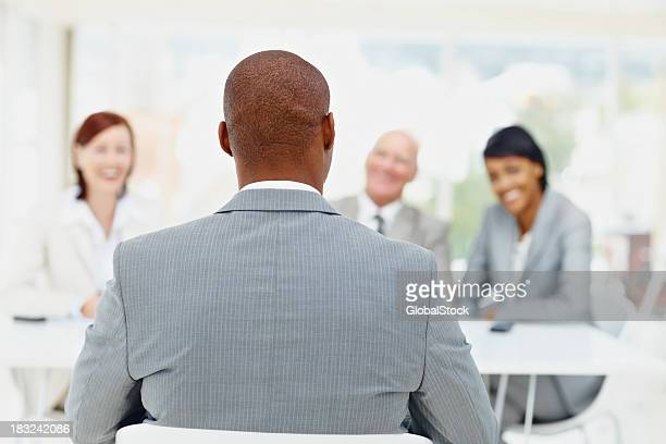 African American man being interviewed by business people