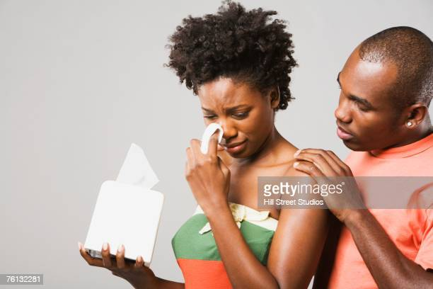African American man comforting crying girlfriend