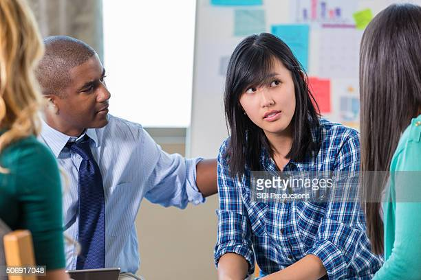 African American man comforts Asian woman in support group therapy