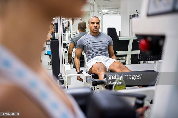 African American man doing leg workouts in a gym.