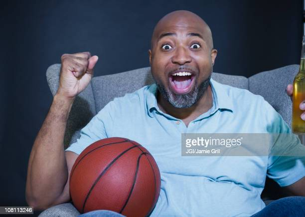 African American man drinking beer and watching basketball on television