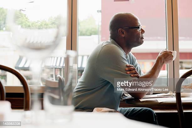 African American man drinking coffee in restaurant