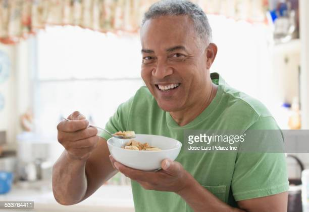 African American man eating bowl of cereal in kitchen