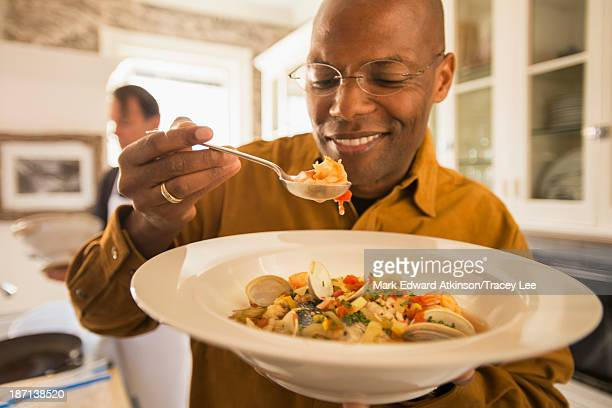 African American man eating seafood stew