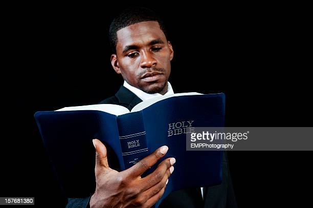 African American Man Holding a Bible Isolated on Black
