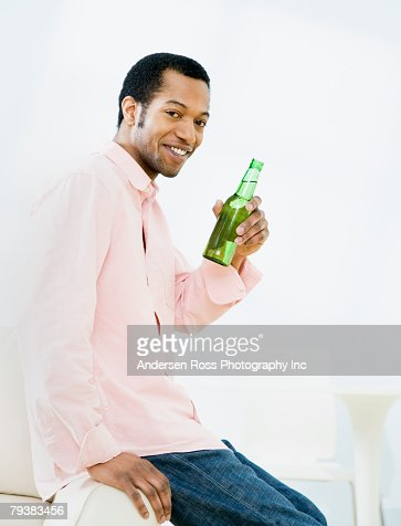 African American man holding bottle of beer : Stock Photo