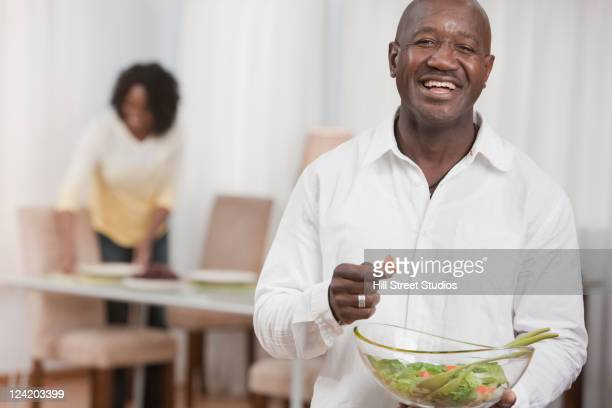 African American man holding bowl of salad