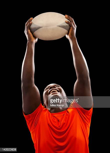 African American man holding rugby ball