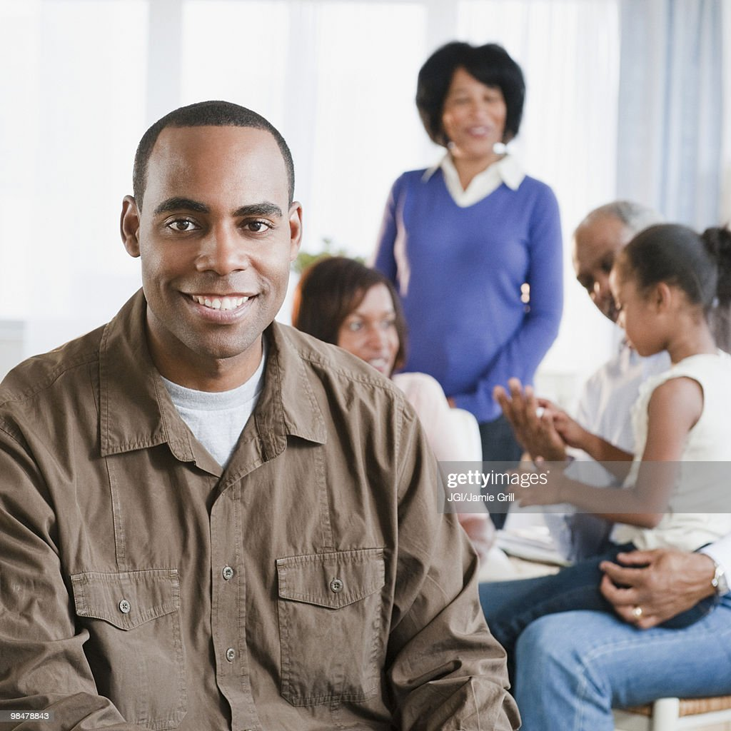 African American man in living room with family : Stock Photo