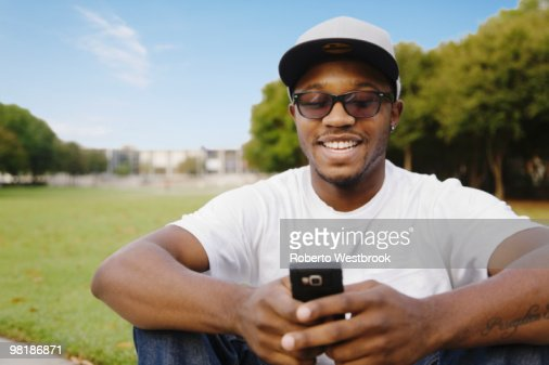 African American man in park using cell phone : Stock Photo