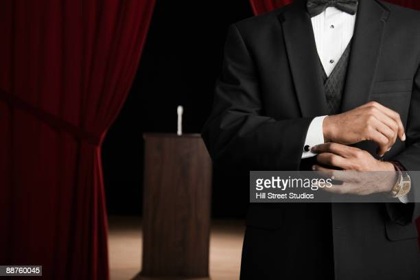 African American man in tuxedo adjusting cufflinks backstage