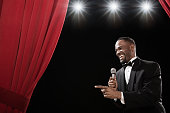 African American man in tuxedo holding microphone onstage