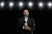 African American man in tuxedo holding trophy