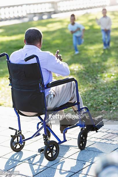 African American man in wheelchair watching kids play