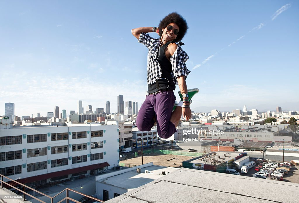 African American man jumping for joy on urban rooftop