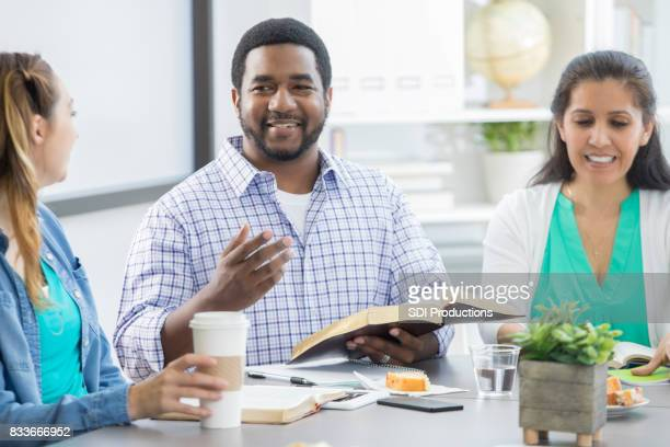 African American man leads office Bible study