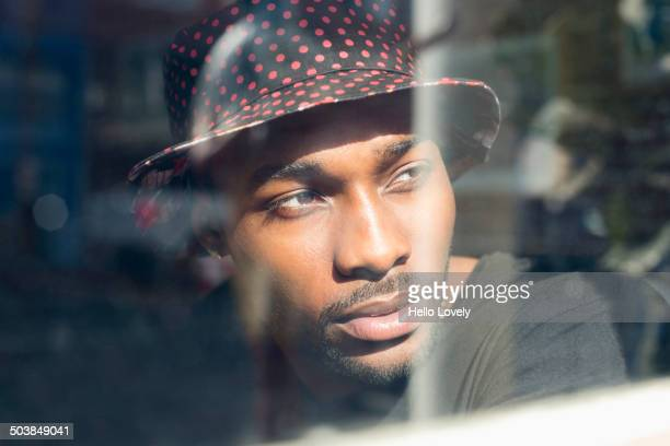 African American man looking out window