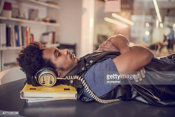 African American man lying on table and listening music.
