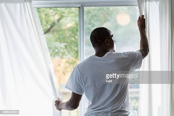 African American man opening curtains on sunny morning