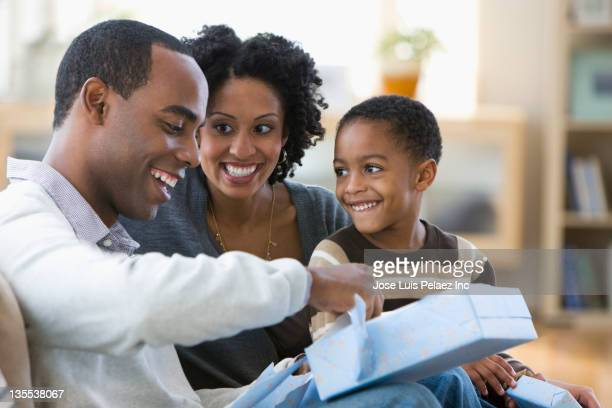 African American man opening gift from family