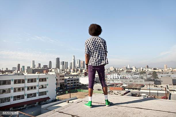 African American man overlooking cityscape from urban rooftop
