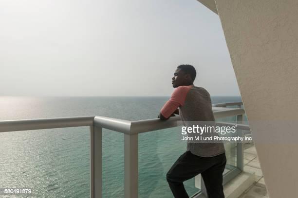 African American man overlooking ocean from balcony